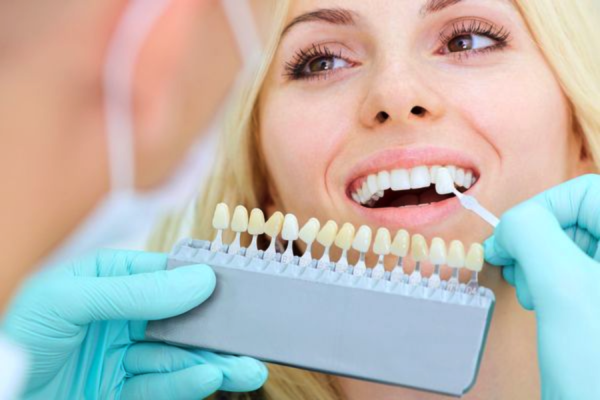 a blonde woman smiling while she receives dental implants